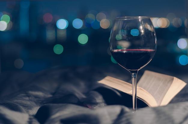 Vaso de vino tinto puesto en cama con libro