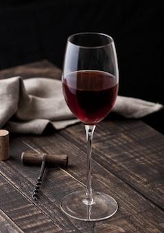 Vaso de vino tinto y sacacorchos vintage en la cocina en la mesa de madera