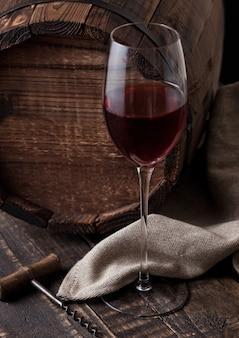 Vaso de vino tinto y sacacorchos vintage y viejo barril en mesa de madera