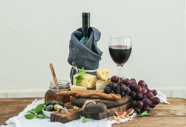 Vaso de vino tinto, tabla de quesos, uvas, higos, fresas, miel y palitos de pan en la mesa de madera rústica