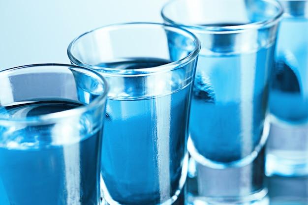 Vaso de vodka con hielo en azul