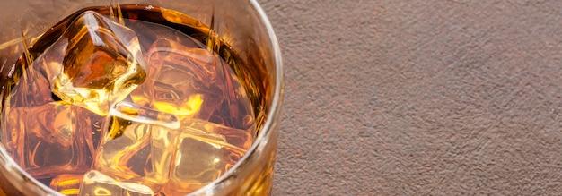 Vaso de whisky de ángulo alto con hielo y espacio de copia