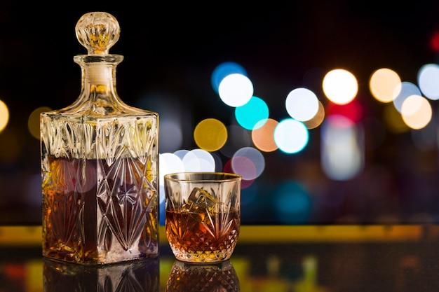 Vaso de whisky y botella con efecto bokeh.