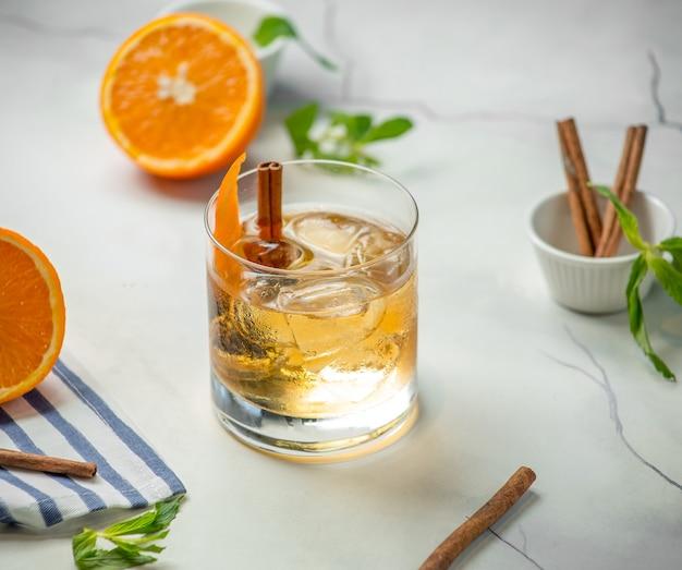 Vaso de whisky con canela sobre la mesa