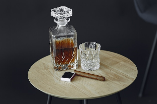 Vaso de whisky con cigarro en la mesa. ciérrese encima de la foto del alcohol y del cigarro.