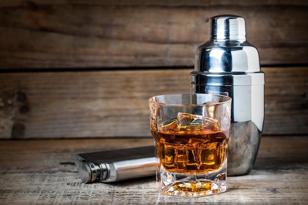Vaso de whisky con una coctelera