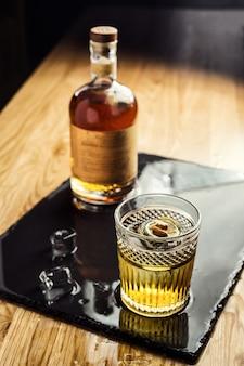 Vaso de whisky (coñac o brandy) con cubitos de hielo en la mesa oscura con una botella