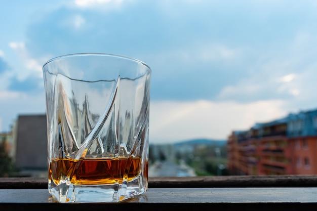 Un vaso de whisky contra el cielo cubierto.