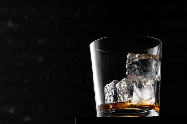 Vaso de whisky contra la pared oscura del grunge negro