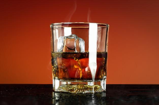 Vaso de whisky y cubitos de hielo en rojo