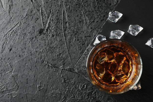 Vaso de whisky y cubitos de hielo sobre fondo negro, vista superior