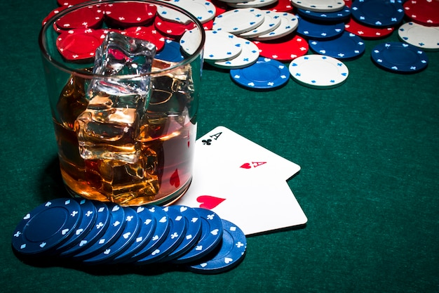 Vaso de whisky con cubitos de hielo sobre la mesa de juego