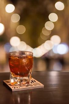 Vaso de whisky con efecto bokeh.