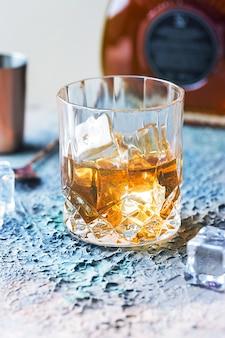 Vaso de whisky escocés con cubitos de hielo, botella y accesorios de barra de cobre