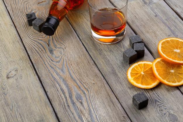 Vaso de whisky con fruta naranja cortada en madera oscura