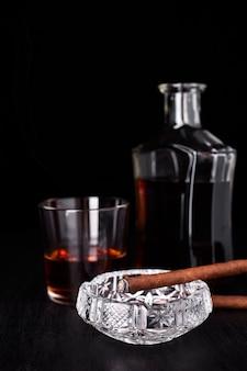 Vaso de whisky con fumar cigarro. whisky, tabaco.