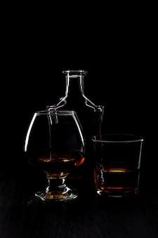 Vaso de whisky con fumar cigarro.