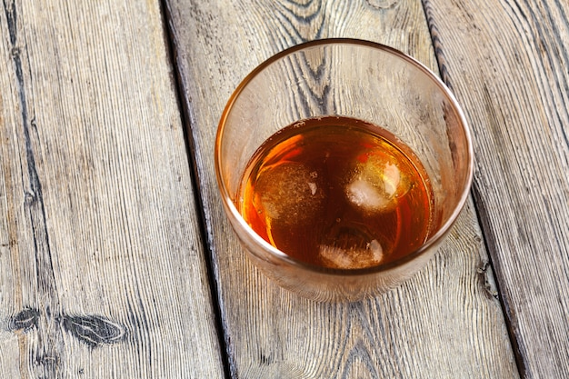Vaso de whisky en hielo con botella en barra de madera