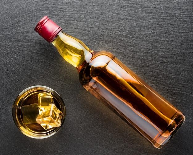 Vaso de whisky con hielo y botella.
