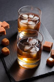 Vaso de whisky con hielo y caramelos de caramelo en un tablero de pizarra de piedra negra sobre superficie negra. vista lateral, bajo perfil.