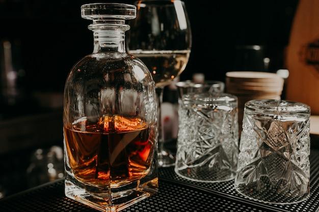 Vaso de whisky con hielo y un decantador cuadrado aislado en