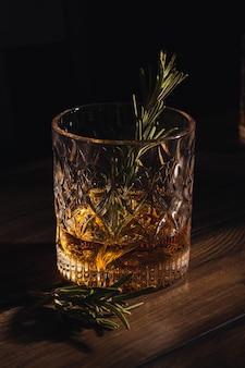 Vaso de whisky con hielo y romero en una mesa de madera