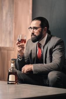 Vaso de whisky. hombre elegante barbudo vestido con corbata roja y traje gris oscuro bebiendo un vaso de whisky