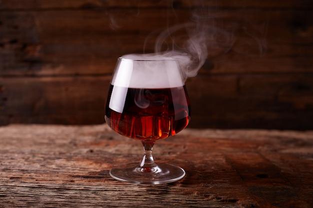 Vaso de whisky en mesa de madera