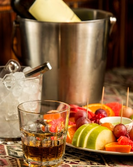 Vaso de whisky y un plato de fruta.