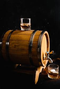 Un vaso de whisky sentado en un barril de madera.