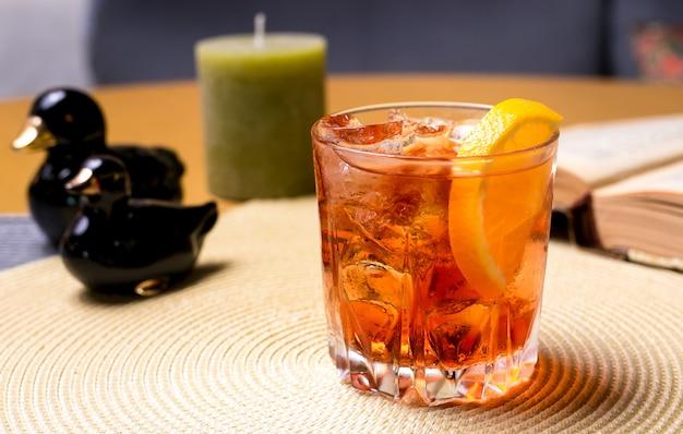 Un vaso de whisky sobre la mesa con rodajas de limón y hielo vista lateral