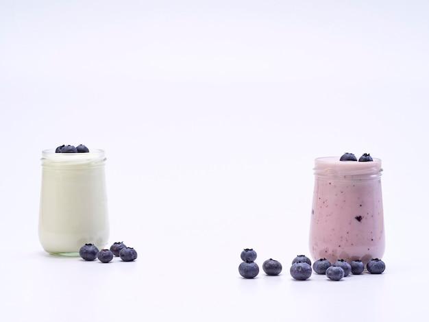 Vaso de yogur de arándanos frescos sobre un fondo blanco.