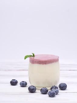 Vaso de yogur de arándanos en mesa de madera blanca