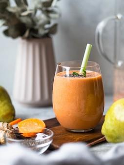 Vaso de zanahoria fresca saludable, pera, batido de jengibre con semillas de chia sobre fondo gris