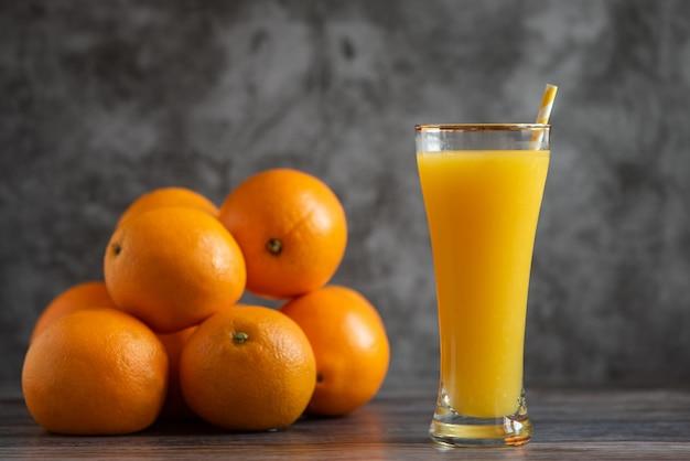 Vaso de zumo de naranja recién exprimido de pie sobre gris con naranjas frescas.