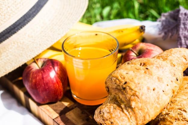 Un vaso de zumo en una tabla junto a croissants y frutas.