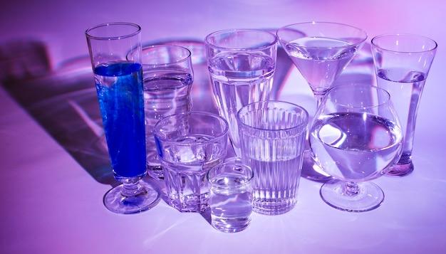 Vasos de agua con cóctel azul sobre fondo coloreado