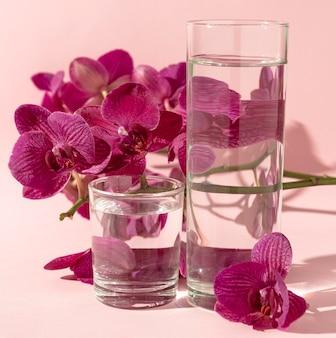 Vasos con agua junto a flores.