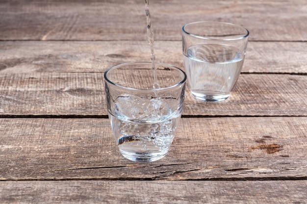 Vasos de agua sobre una mesa de madera.