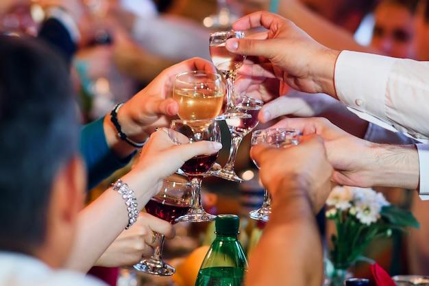 Vasos de alcohol en manos de amigos celebrando la fiesta