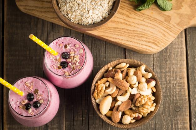 Vasos de batido de bayas con nueces, menta, arándano, frambuesa y yogurt en mesa de madera. pérdida de peso y dieta.