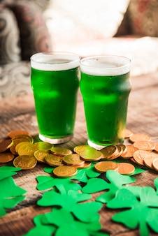 Vasos de bebida verde cerca de montón de monedas y tréboles de papel