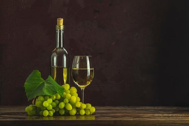 Vasos y botellas de vino blanco y uvas sobre fondo de superficie de hormigón burdeos clarete oscuro