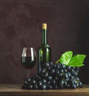 Vasos y botellas de vino y uvas sobre fondo de superficie de hormigón burdeos clarete oscuro