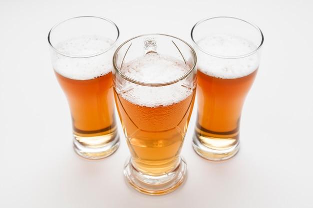 Vasos de cerveza dorada de alto ángulo