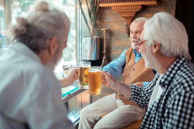 Vasos con cerveza. hombres canosos barbudos sonriendo mientras golpean vasos con cerveza