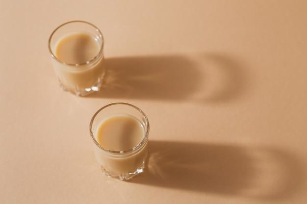 Vasos cortos de licor de crema irlandesa o licor de café sobre fondo beige claro
