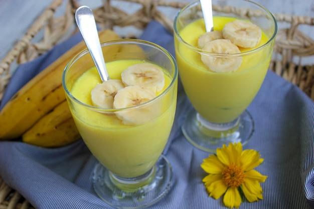 Vasos con delicioso pudín de plátano en la bandeja para el desayuno