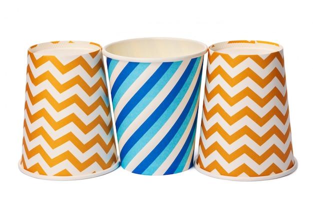 Vasos desechables de papel con patrón de colores aislado sobre fondo blanco.