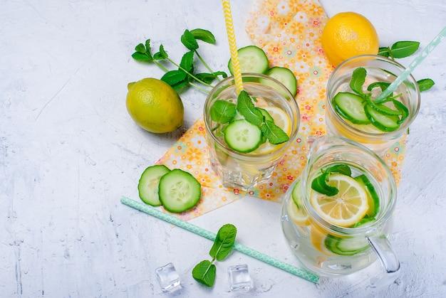 Vasos con desintoxicación de pepino orgánico fresco, agua de menta y limón en mesa blanca